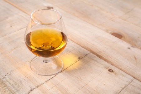 distillate: Snifter glass with amber colored brandy on a grunge wooden table