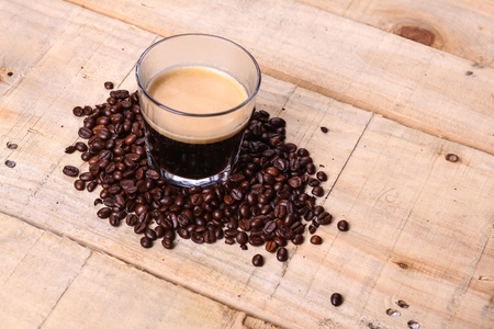 tumbler glass: Tumbler glass with fresh coffee surrounded by roasted coffee beans over a grunge wooden background