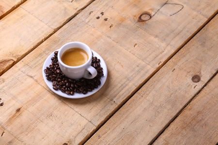 Small cup of fresh espresso coffee on a saucer with roasted coffee beans over a gunge wooden background Stock Photo