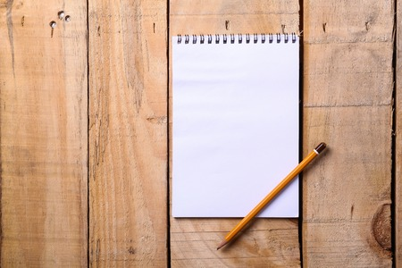 blank note: Blank white notepad with pencil on a grunge wooden surface
