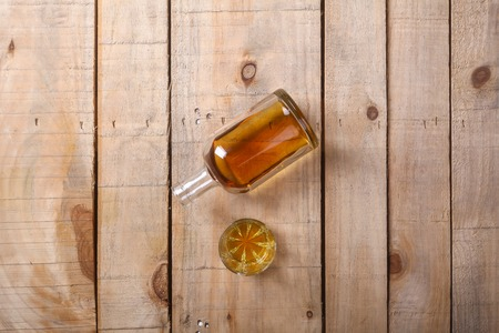 tumbler glass: Bottle of brandy with a tumbler glass on a grunge wood surface Stock Photo