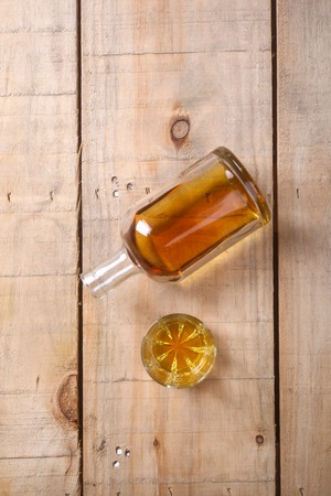 grunge bottle: Bottle of brandy with a tumbler glass on a grunge wood surface Stock Photo