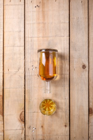 tumbler: Bottle of brandy with a tumbler glass on a grunge wood surface Stock Photo