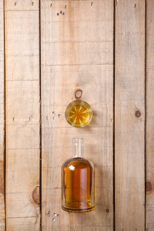 distillate: Bottle of brandy with a tumbler glass on a grunge wood surface Stock Photo