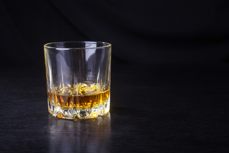 tumbler glass: Tumbler glass with some whiskey on a black wooden surface Stock Photo