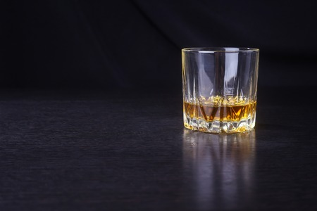 distillate: Tumbler glass with some whiskey on a black wooden surface Stock Photo