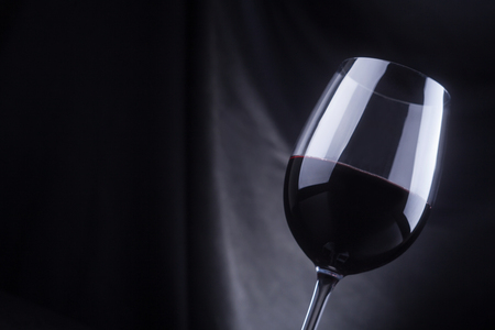 redwine: Glass of red wine on a dark wooden surface with a dark background Stock Photo