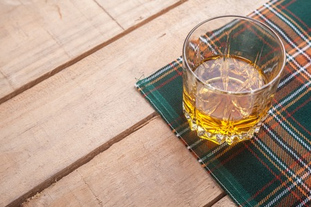 scotch whisky: Glass of Scotch whisky on a traditional tartan cloth on a wooden table Stock Photo