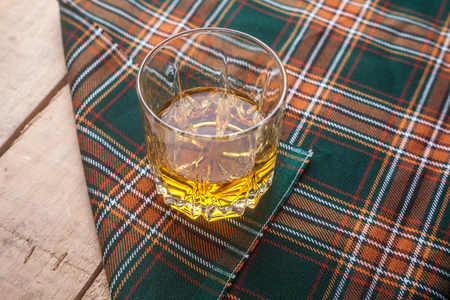Glass of Scotch whisky on a traditional tartan cloth on a wooden table Stock Photo
