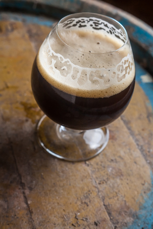 ale: Snifter glass full of dark ale standing on a wooden barrel in a cellar Stock Photo