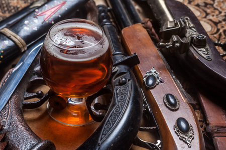 ipa: Snifter glass with pale ale beer surrounded by antique guns and knifes Stock Photo