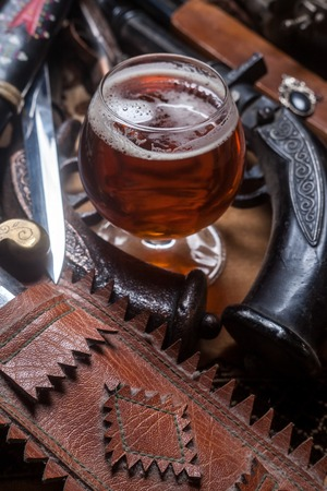 weaponry: Snifter glass with pale ale beer surrounded by antique guns and knifes Stock Photo