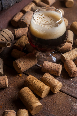 maturation: Snifter glass with dark ale beer in a cellar with wine corks Stock Photo