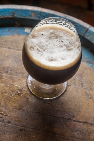 maturation: Snifter glass full of dark ale standing on a wooden barrel in a cellar Stock Photo