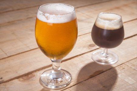 ipa: Small glass of dark beer and larger glass of light beer on a wooden table