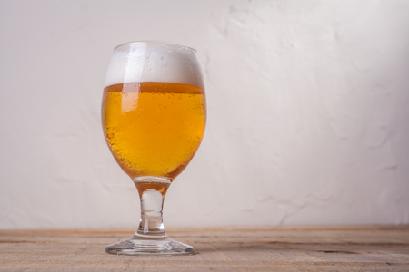 ipa: Glass of light beer with tall white foam head on a wooden table