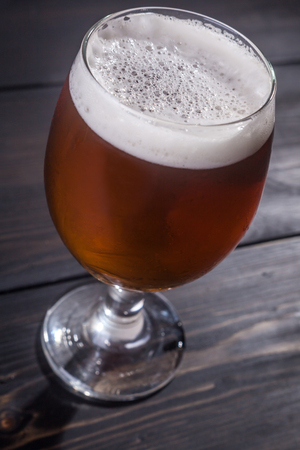 ipa: Glass full of amber ale on a dark wooden table