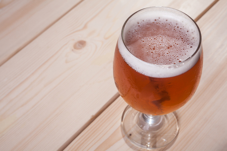 ale: Glass full of amber ale on a smooth wooden surface