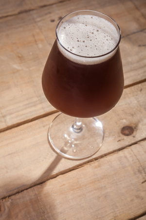 ale: Tulip glass full of brown ale on a grunge wooden surface
