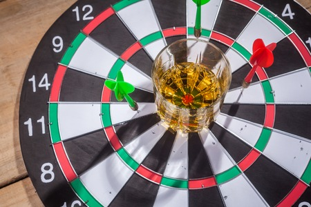 tumbler: Tumbler glass with whiskey standing on a darts game target