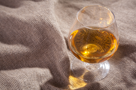 Snifter glass with brandy standing on hard sackcloth Stock Photo