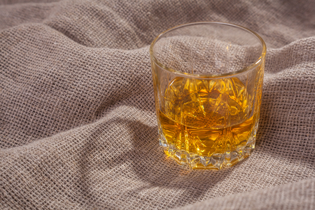 tumbler: Tumbler glass of amber colored whiskey over a textured sackcloth Stock Photo