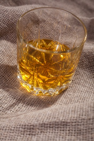 tumbler glass: Tumbler glass of amber colored whiskey over a textured sackcloth Stock Photo