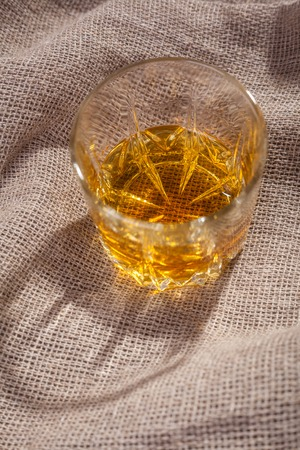 sackcloth: Tumbler glass of amber colored whiskey over a textured sackcloth Stock Photo