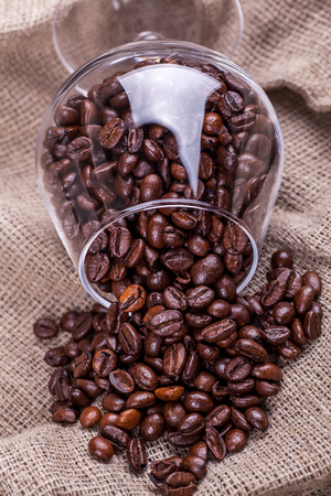 sackcloth: Glass full of roasted coffee beans overturned on sackcloth