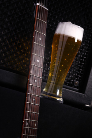 near beer: Tall glass full of light beer standing near a grilled music monitor with a guitar fretboard in the foreground