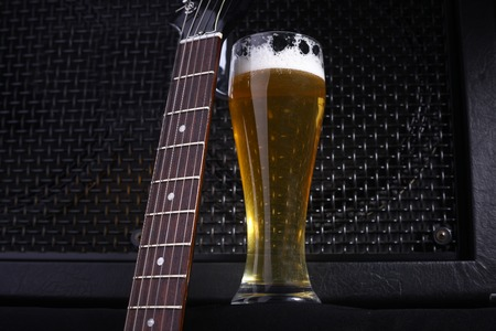 fretboard: Tall glass full of light beer standing near a grilled music monitor with a guitar fretboard in the foreground