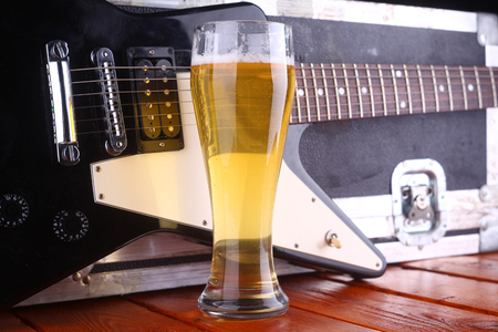 Tall glass full of light beer standing on a wooden table with a music equipment case and guitar in the background