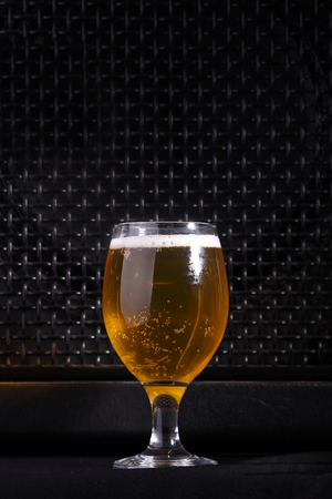 near beer: Glass full of light beer standing near a big grilled music monitor