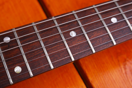 fretboard: Closeup of an electric guitar fretboard over a wooden surface