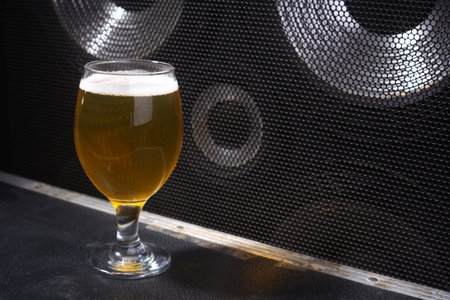 near beer: Glass full of light beer standing on a music equipment crate near a big grilled music monitor Stock Photo