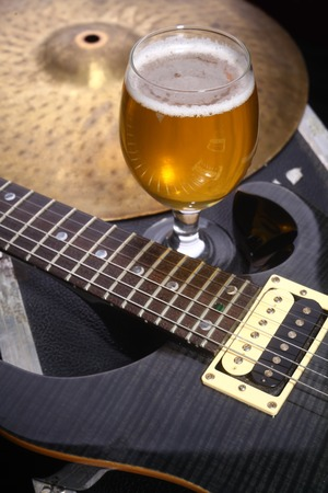 Glass full of light beer standing on a case with some music equipment Stock Photo