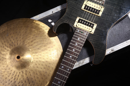 cymbal: Electric guitar and cymbal lying on a music equipment case