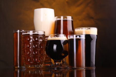 beer tulip: An assortment of various beer glass shapes and styles on a wooden table with a drapery in the background