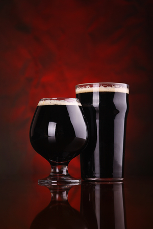 pint: Nonic pint and snifter of dark beer on a wooden table over a reddish background