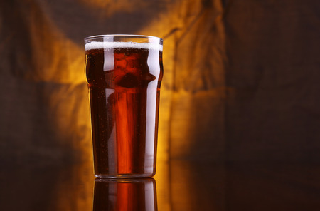 Nonic pint glass with light beer with a warm colored drapery in the background