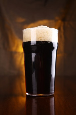 Nonic pint of dark beer on a table with a warm colored drapery in the background Stock Photo
