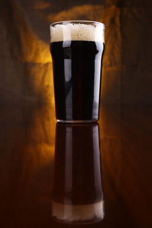 pint: Nonic pint of dark beer on a table with a warm colored drapery in the background Stock Photo
