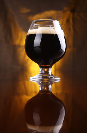 snifter: Snifter glass with black beer on a wooden table with a warm colored drapery in the background