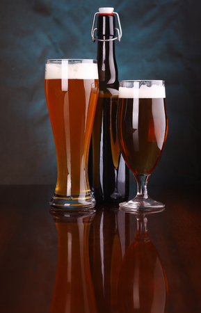 beer tulip: Glasses and bottle of light beer on a wooden table with a blue lit background Stock Photo