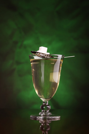 decadence: Glass of absinthe with a special spoon and sugar cubes over a green backdrop