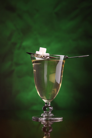 distillate: Glass of absinthe with a special spoon and sugar cubes over a green backdrop