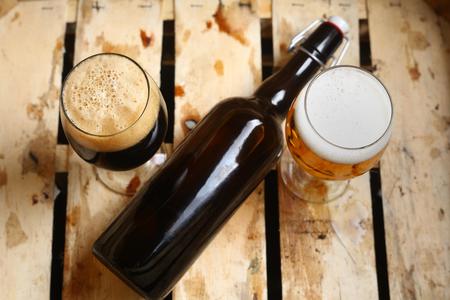Botella y vasos llenos de cerveza mirando un signo de porcentaje en una caja de madera sucia