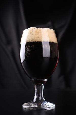 beer tulip: Small tulip glass full of dark beer over a dark background