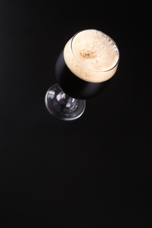 topdown: Small tulip glass full of dark beer over a dark background
