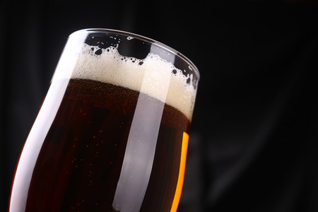 ale: Tall tulip glass of amber ale over a dark background